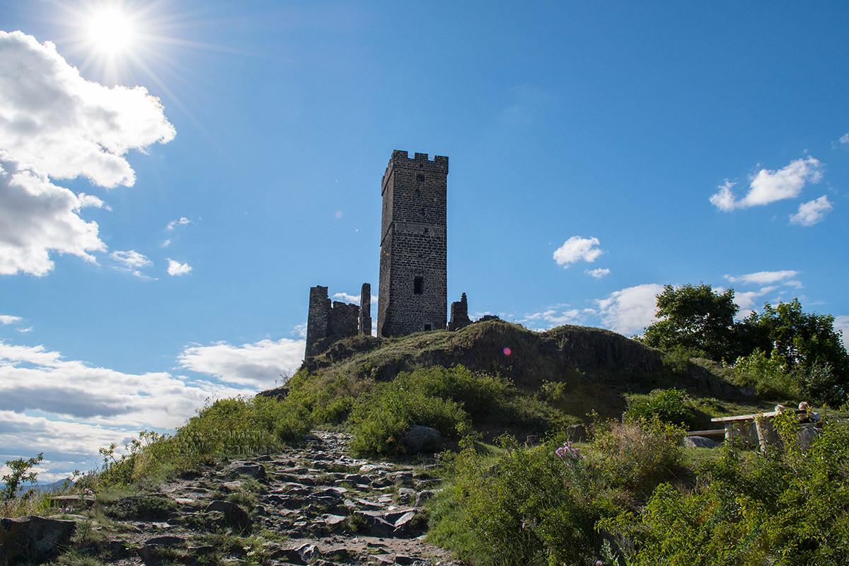 Западнее квадратной башни скалистый массив, на котором стоит замок Хазмбурк, резко обрывается, обнажая каменный утес.