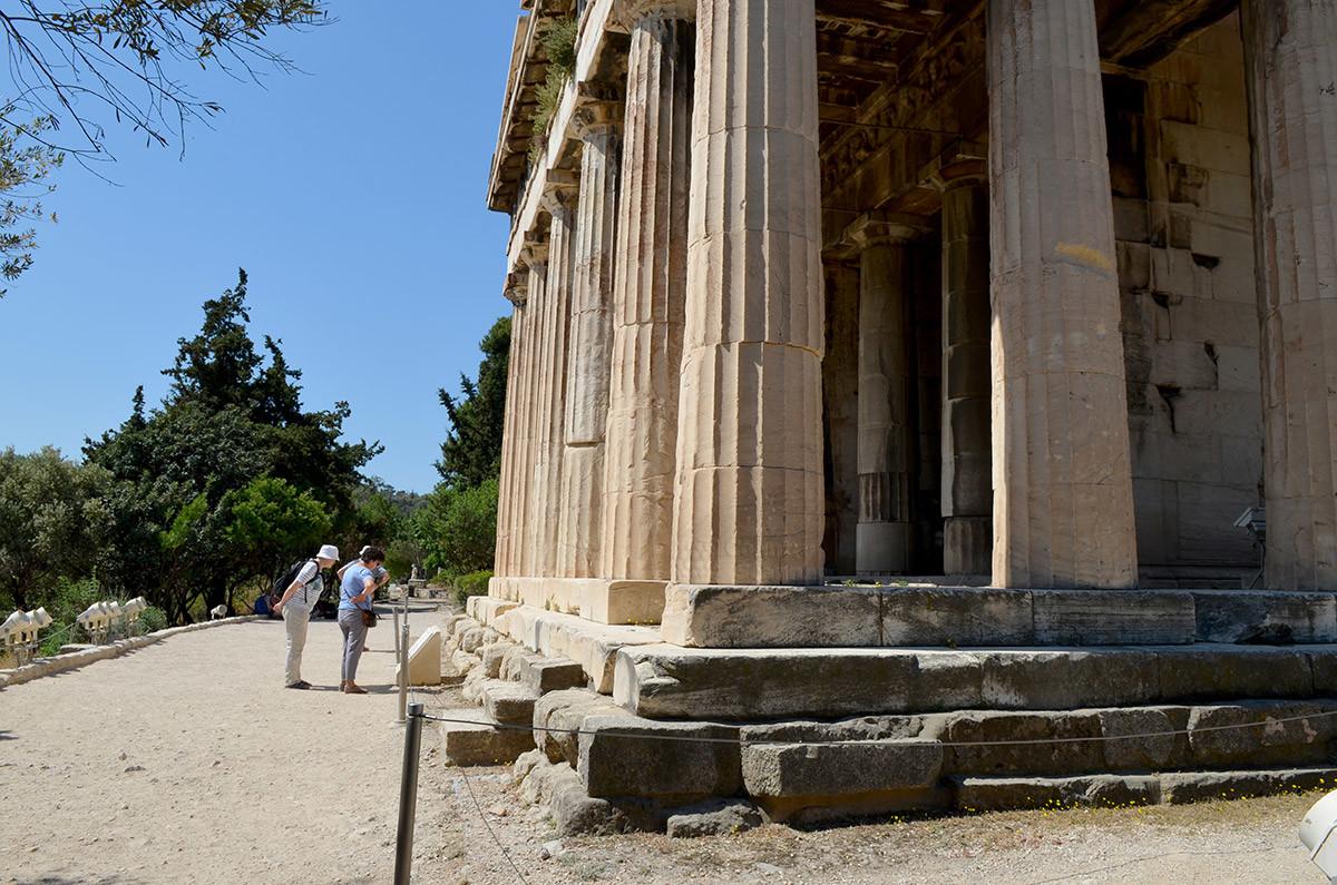Посещающие храм Гефеста любознательные туристы внимательно изучают пояснительные надписи.