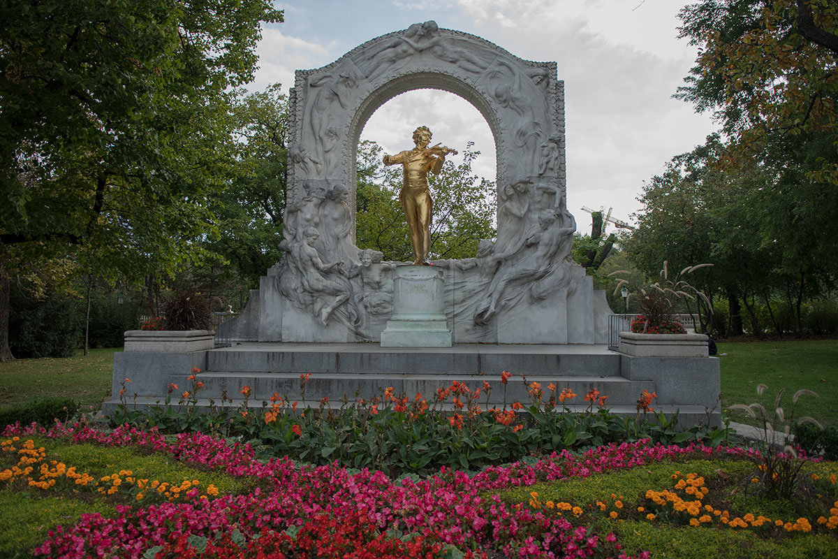 Густая парковая зелень и цветник у подножия удачно дополняют памятник Штраусу.