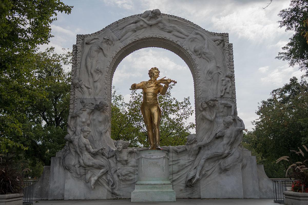Позолоченный скрипач памятника Штраусу играет на фоне мраморной арки с танцующими русалками, чьи движения подхватывают вальсовую мелодию.