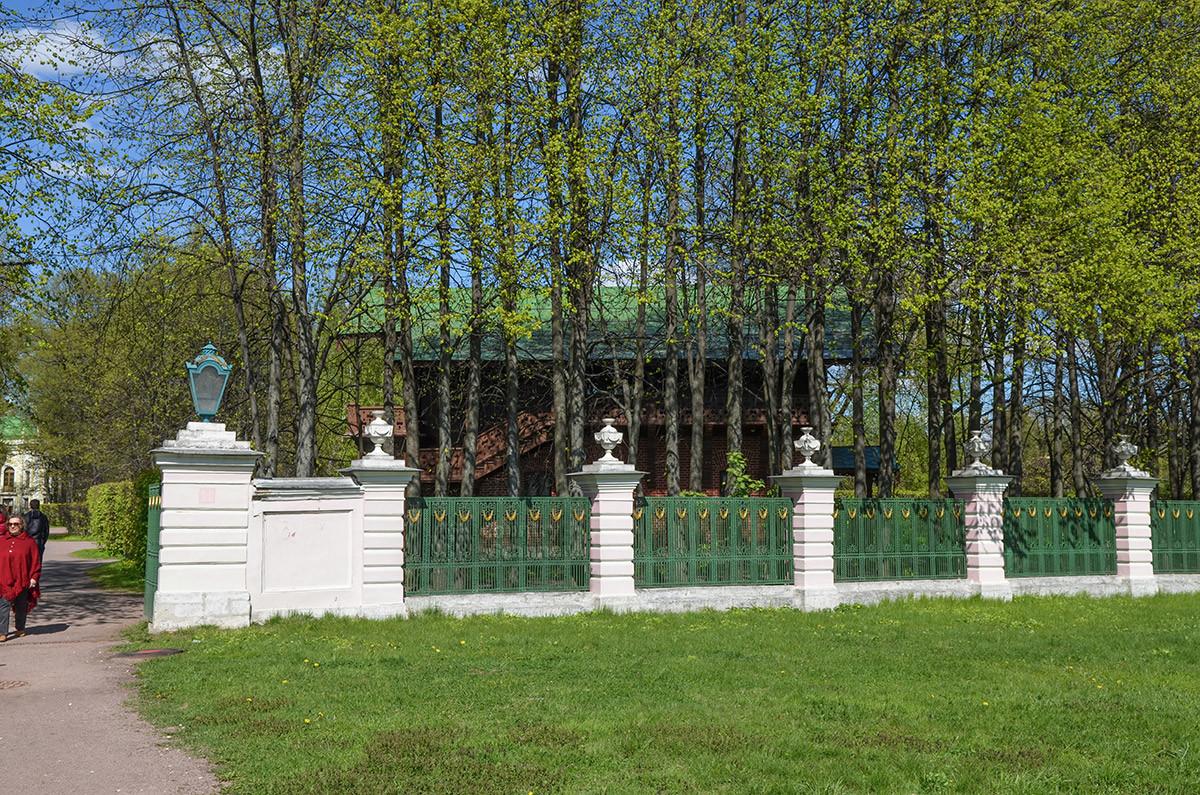 Из-за старинной ограды и высоких деревьев швейцарский домик в Кусково выглядитвесьма привлекательно и интригующе.