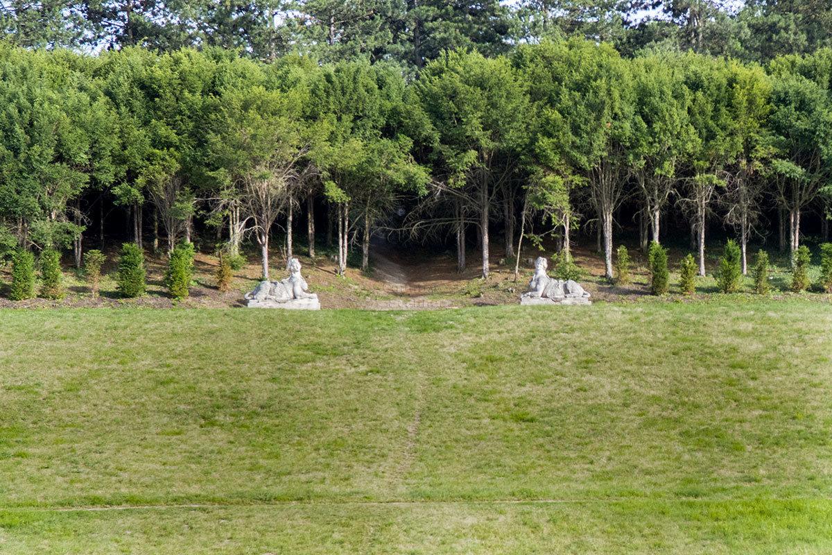 Опушка лесного массива и две аллегорические статуи, ограждающие начало тропинки из Валтице в соседний замок Леднице.