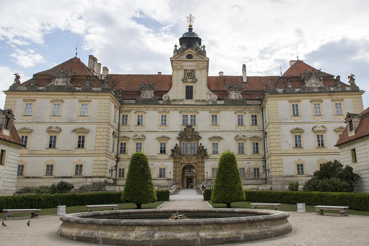Фонтан перед замком Валтице и его центральный фасад, украшенный скульптурами вход, над ним – башенка с часами и крест часовни.