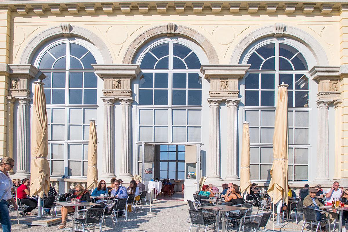 С южной стороны Глориетта обставлена столиками летнего кафе, обслуживающего будущих или бывших посетителей Шенбрунна.
