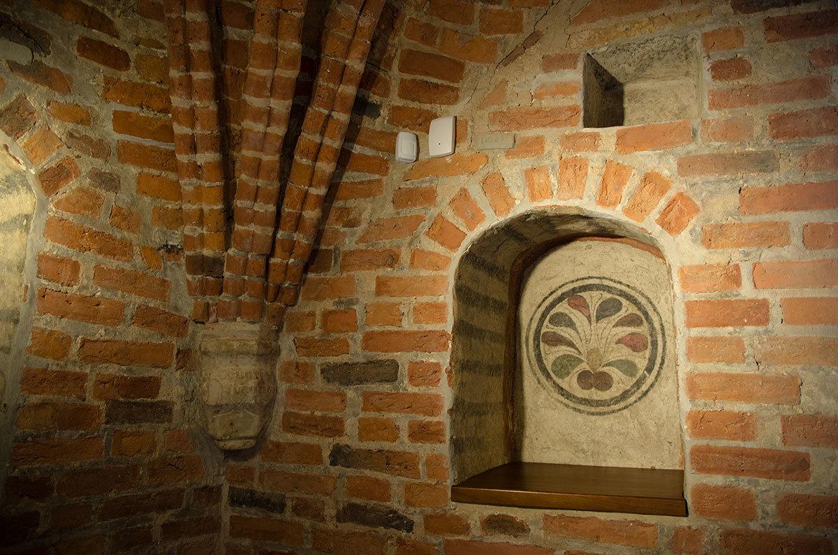 Стилизованный цветок древнего орнамента в нише по соседству с опорной каменной деталью, на которую опираются сходящиеся грани.