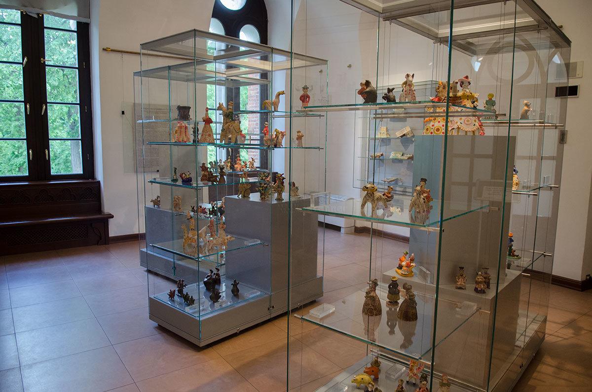 Предметы народного творчества на полках витрин экспозиции Хлебного дома о декоративно-прикладном искусстве.