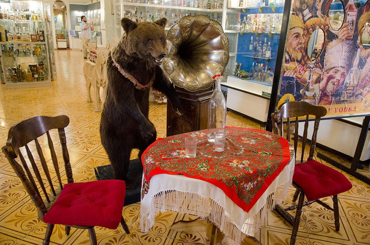Выставленная в музее истории водки объемистая четверть четвертая часть ведра сопровождается чучелом медведя у граммофона.