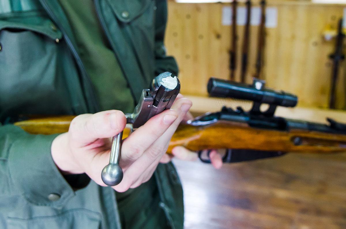 Посетитель музея оружия в Измайловском кремле проводит неполную разборку снайперской модификации винтовки Мосина.