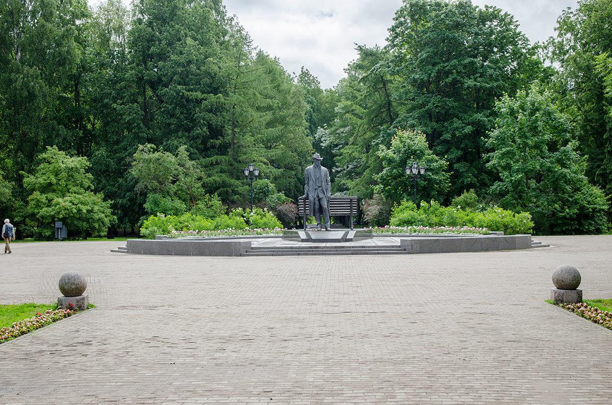 Обзорное фото изображает памятник Рахманинову в Великом Новгороде на фоне Кремлевского парка, окружающего северо-западную часть местного кремля.