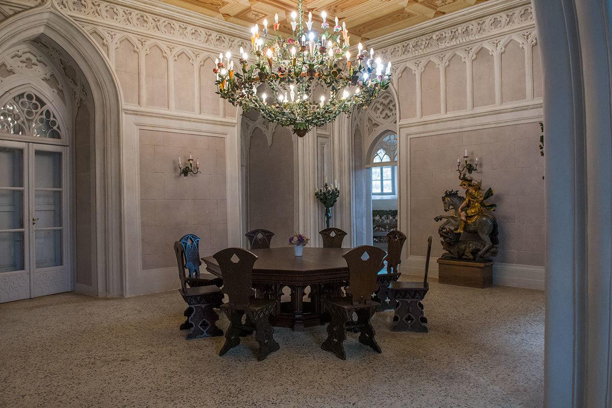 Замок Битов встречает посетителей Рыцарским залом с традиционным столом, массивными стульями и скульптурной группой.