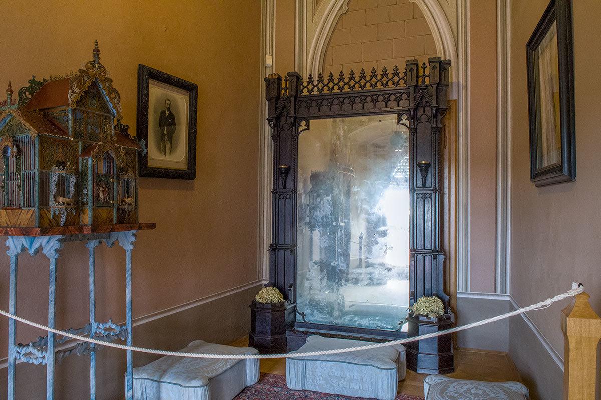 Женский будуар замка Битов примечателен огромным зеркалом с потускневшей амальгамой и резной птичьей клеткой.