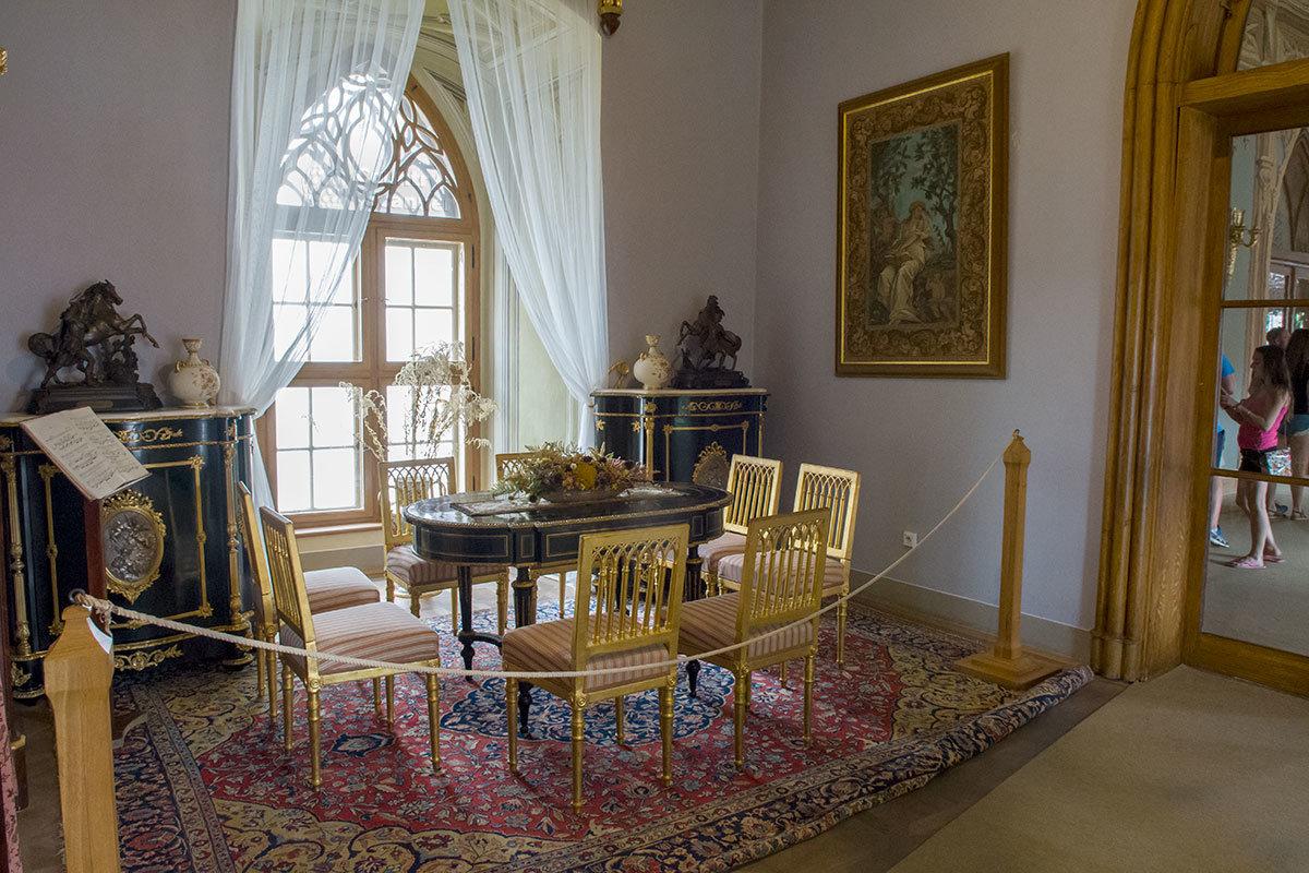 Уникальные мебельные изделия в музыкальном салоне замка Битов изготовлены из темной древесины с металлическими вставками.