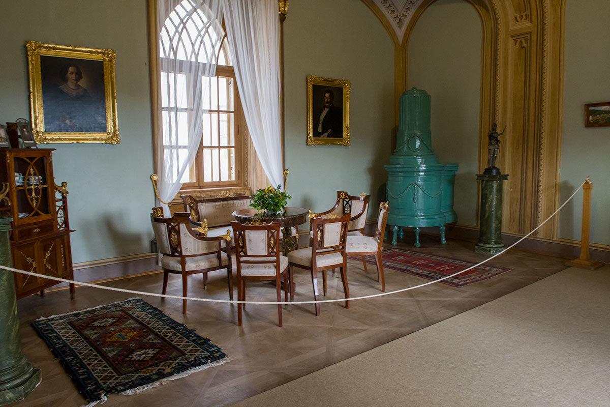 Джентльменский зал замка Битов украшен симметрично расположенными статуэтками на постаментах и портретами на стене.