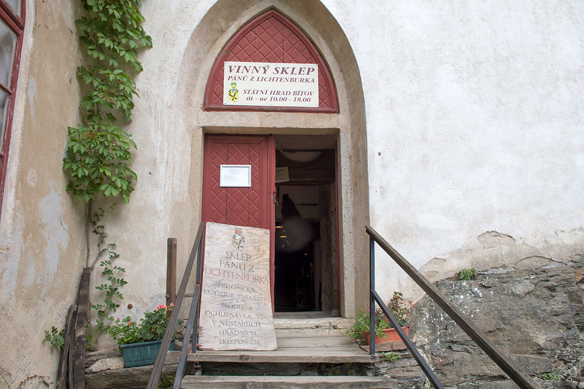 Вход в винный погреб замка Битов с вывесками, свидетельствующими о давней традиции виноделия.