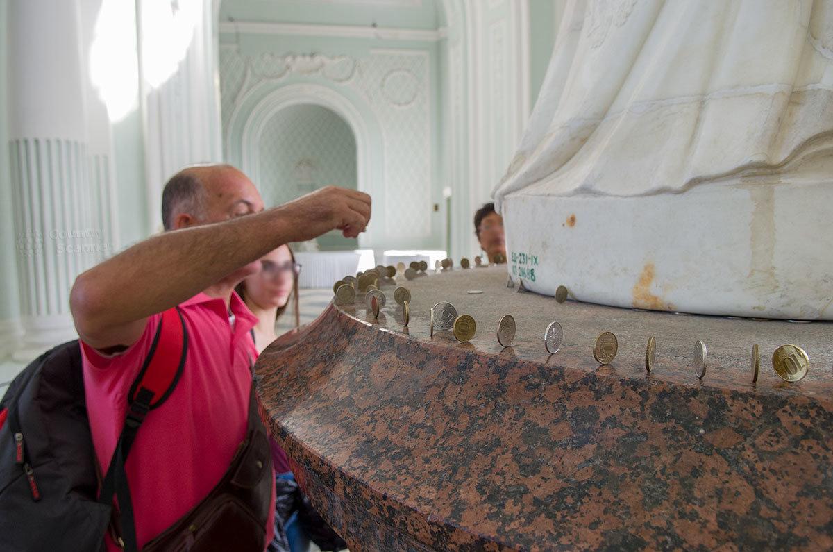 Гранитный постамент статуи Екатерины Великой в Гроте в Царском селе стал ареной нового туристического тренда – выставления монеток на ребро.
