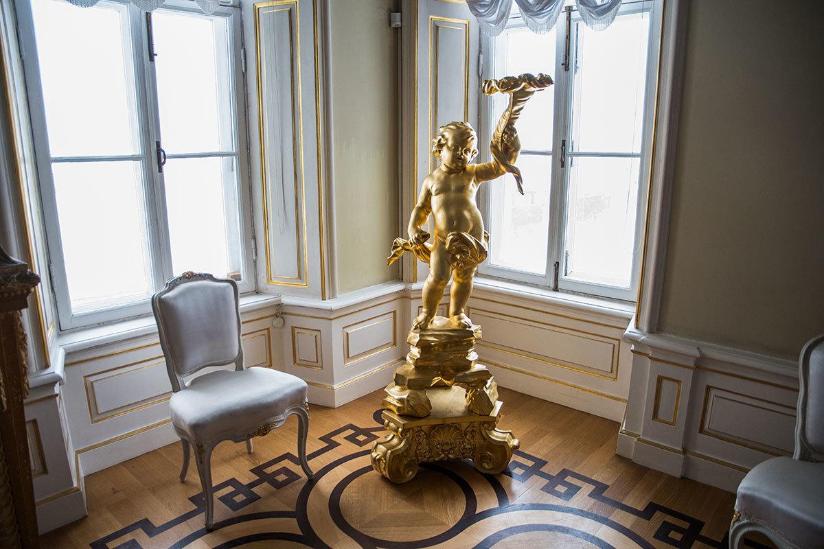 Балансирующий с факелом на дощечке шаловливый Амур – не скульптура только, но и позолоченный канделябр