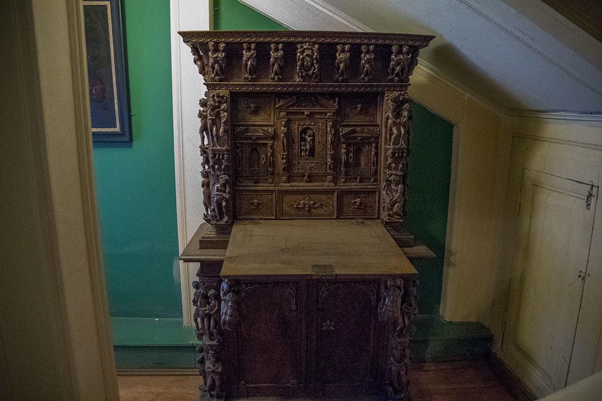 Исключительно тонкой работы резной деревянный секретер со скульптурной резьбой почему-то установлен под лестницей Итальянского домика.