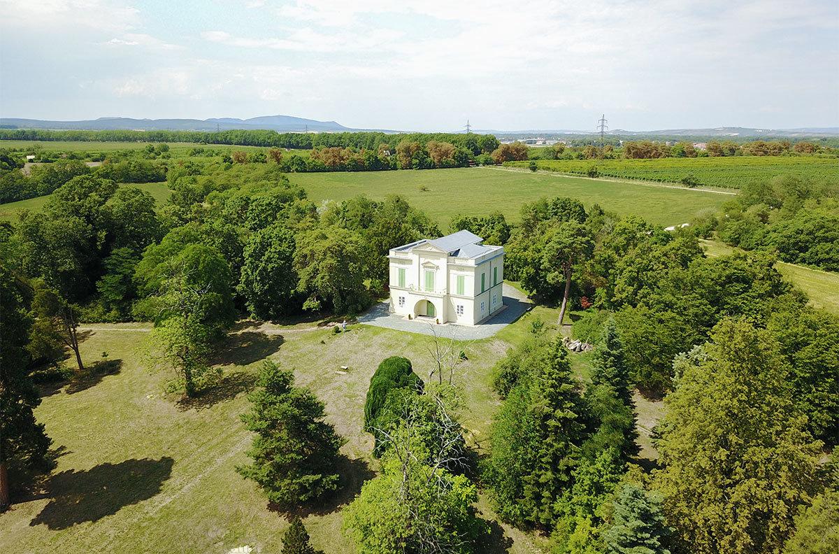 Небольшой по размерам прудовый замок расположен в равнинной местности, в отдалении виднеется поселение Леднице.
