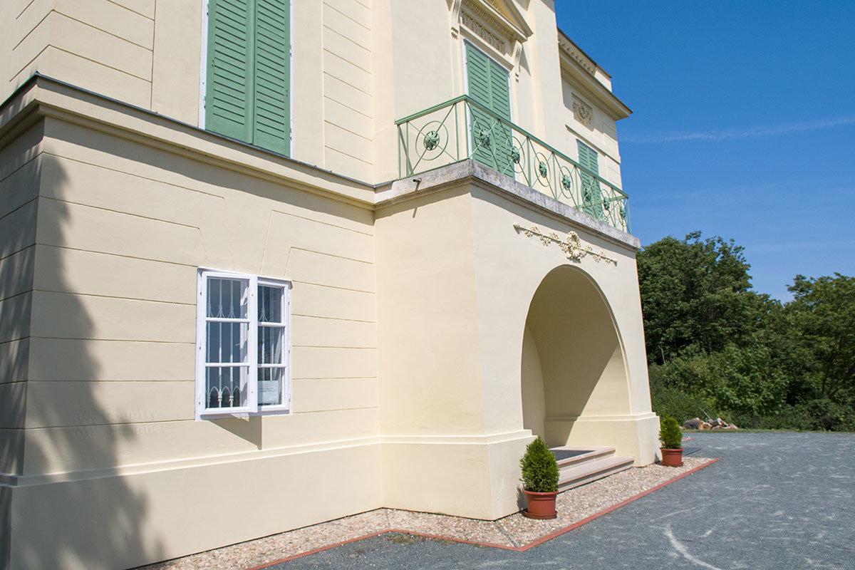 Обращенный к водоему фасад прудового замка выполнен с центральным ризалитом, украшенным входной аркой и балконом.