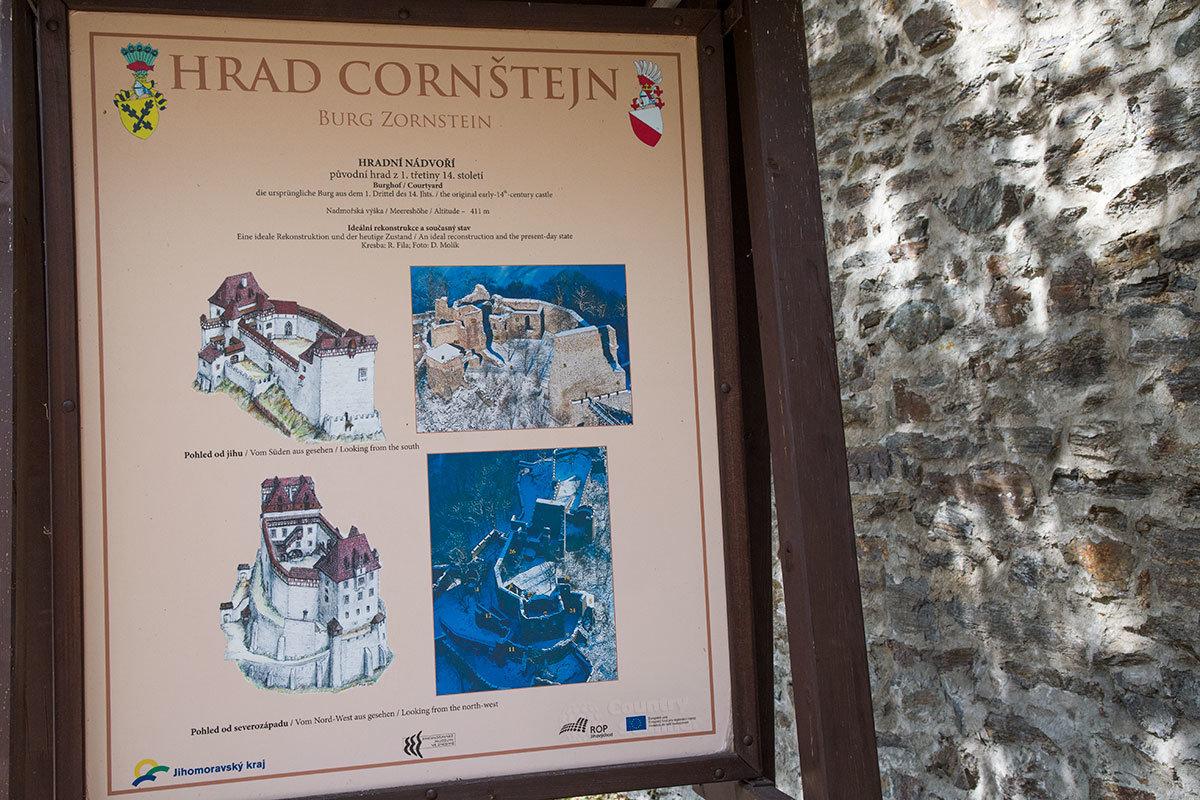 На информационном стенде замок Корнштейн на рисунках предстает в первоначальном виде, на фото – в нынешнем.