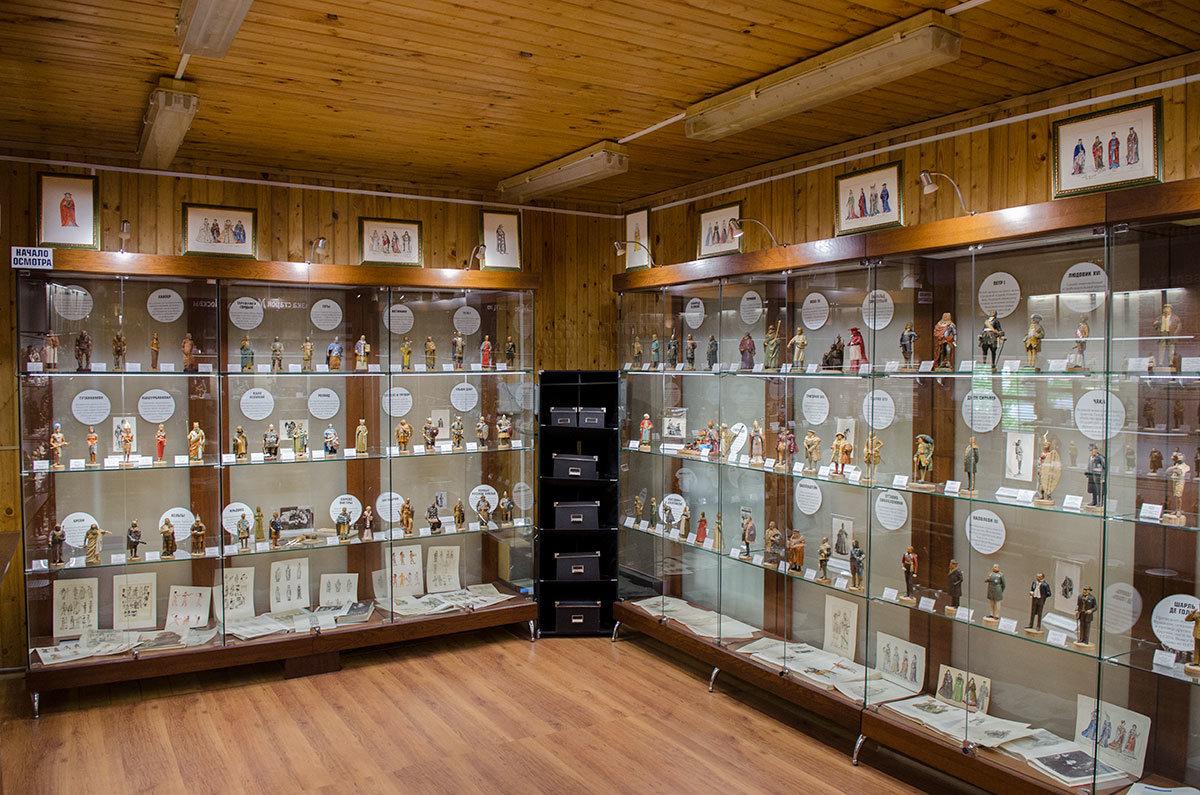 Музей пластилиновой миниатюры оборудован стеклянными витринами, на нескольких рядах полок размещены небольшие фигурки.
