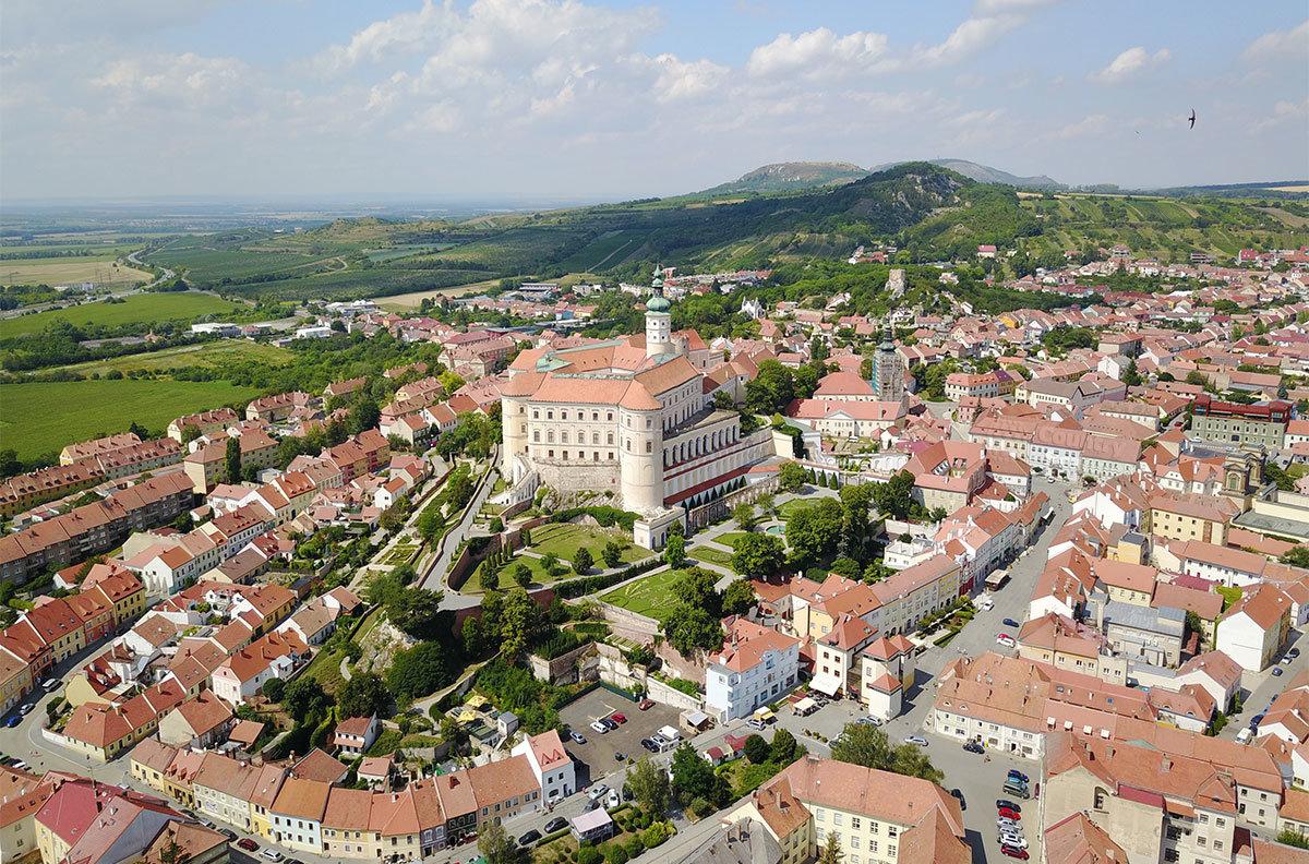 На высотной фотографии замок Микулов выделяется возвышенным расположением, он окружен городскими постройками.