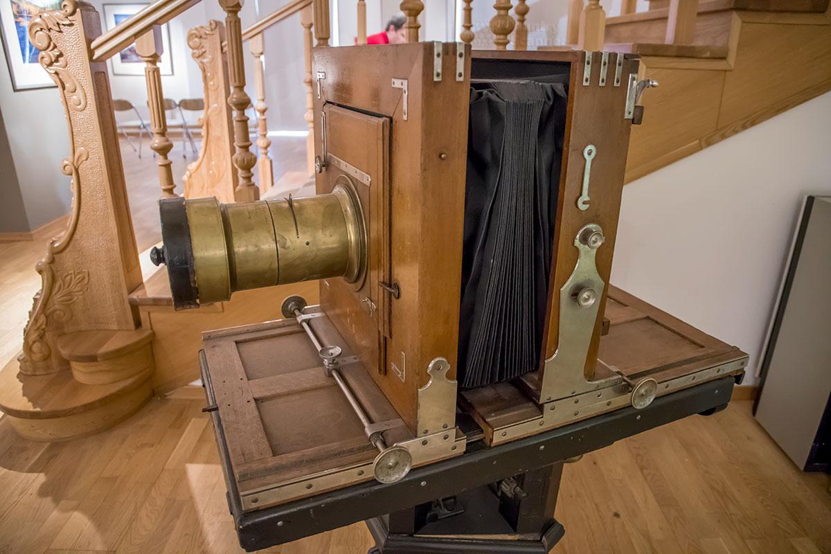 Возле лестницы на второй этаж интерес посетителей галереи классической фотографии привлекает без преувеличения древний фотоаппарат.