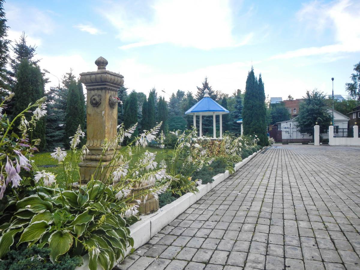 Церковная территория храма Николы Белого полностью замощена тротуарной плиткой, декорирована разнообразной растительностью.