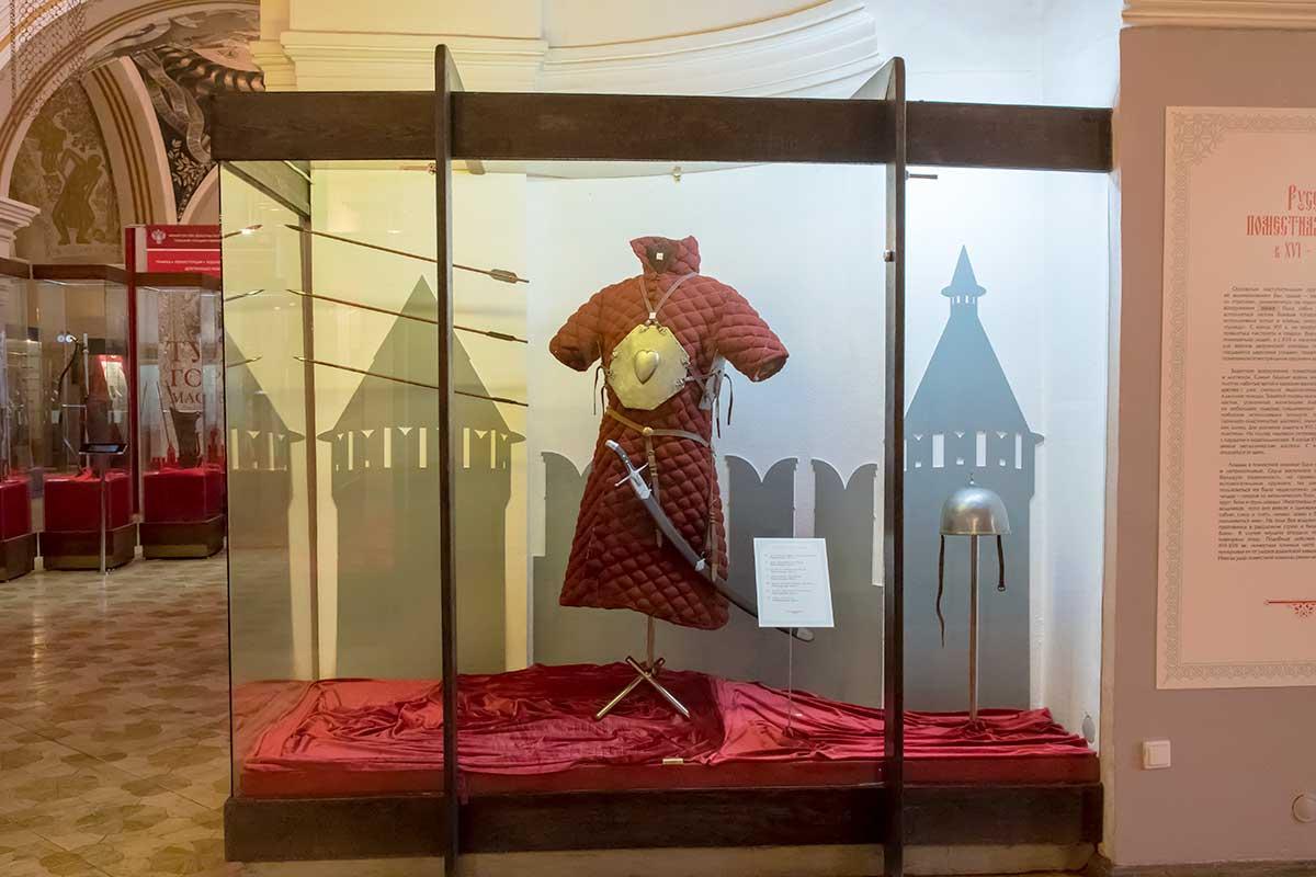 Стеганый кафтан для защиты от стрел выставлен в экспозиции музея оружия в кремле на фоне силуэтов крепостных стен и башен.
