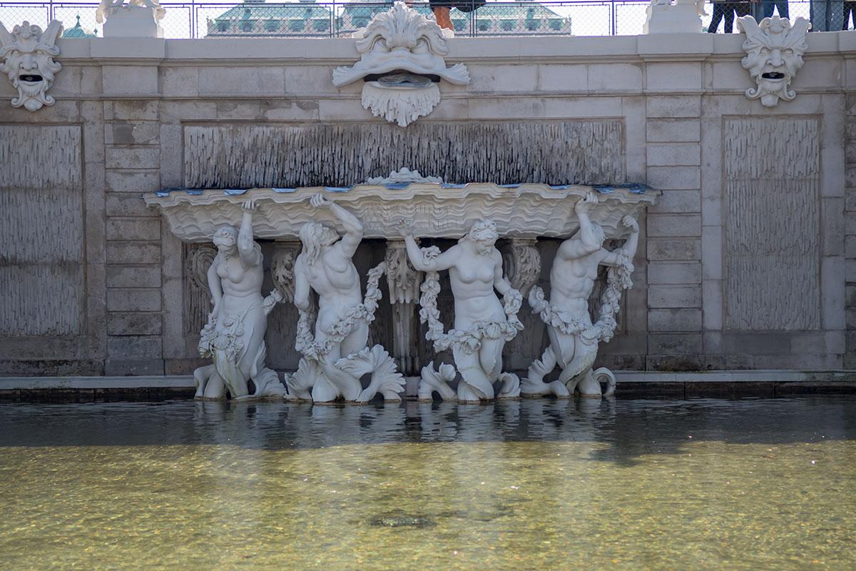 Фигуры мифических речных божеств, удерживающих открытым шлюз воображаемой плотины, украшают второй перепад высот партера комплекса Бельведер в Вене.