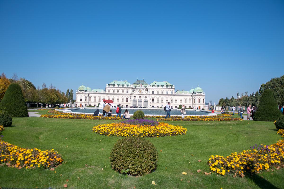 Наблюдаемый издалека дворец Верхний Бельведер в Вене со своей бирюзовой крышей разных уровней гармоничен с окружающей зеленью растительности.
