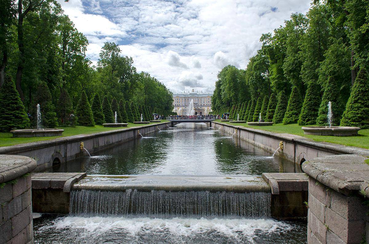 Впечатляющий вид на Морской канал, мосты и зелень с Большим Петергофским дворцом вдали открывается от пристани на Финском заливе.