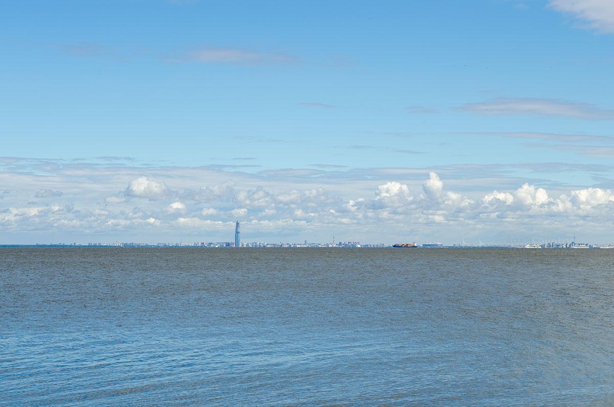 С набережной дворца Монплезир, несмотря на 15 км расстояния, видны строения Санкт-Петербурга, прежде всего высотная контора Газпрома.