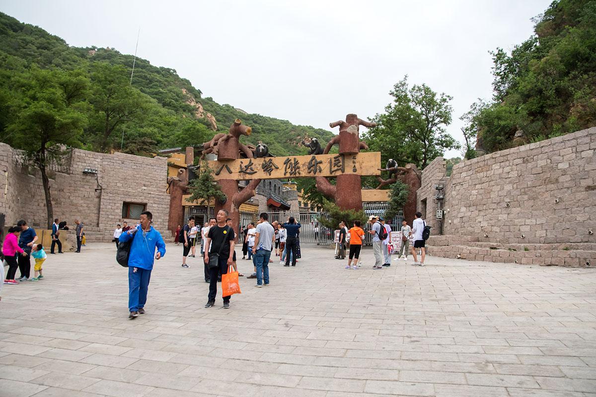 На входной площади у Великой Китайской стены всегда многолюдно, туристов встречает вывески на опорах из стволов вековых деревьев.