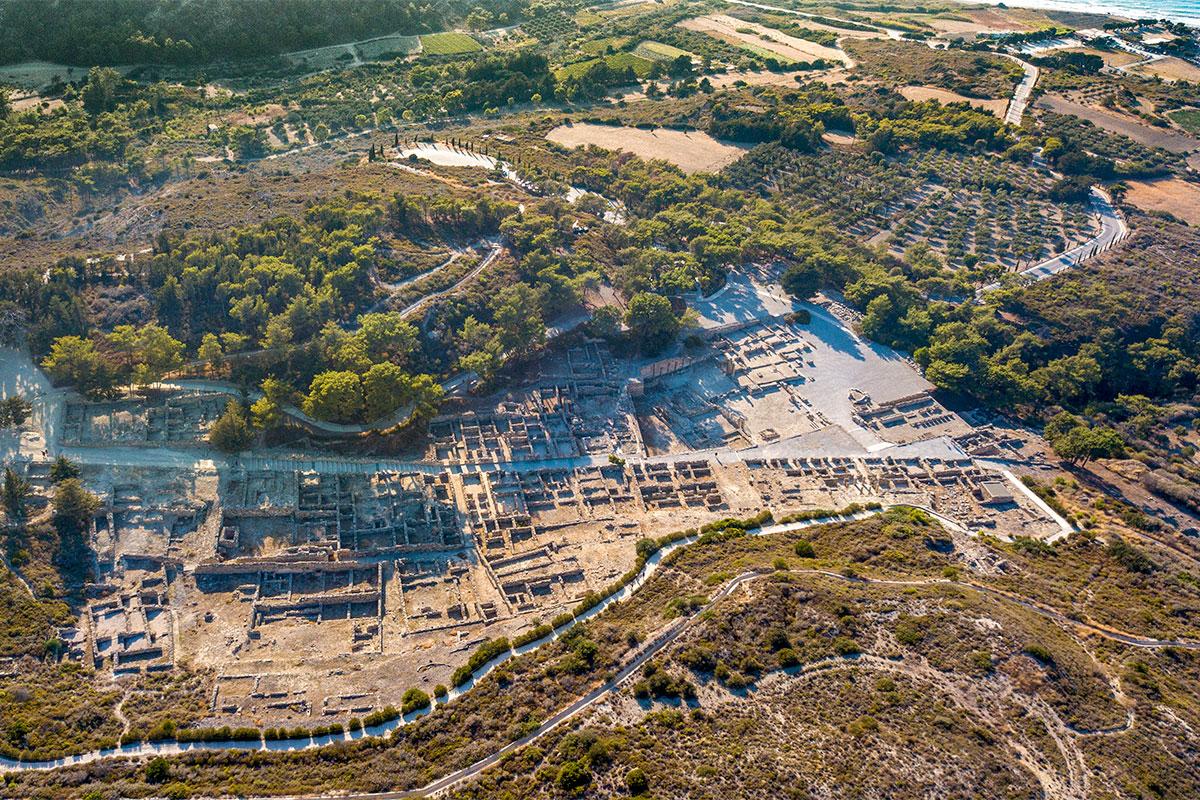 Панорамная высотная фотография охватывает и раскопанный Камирос, и подходящую к нему автодорогу, и сельскохозяйственные угодья.