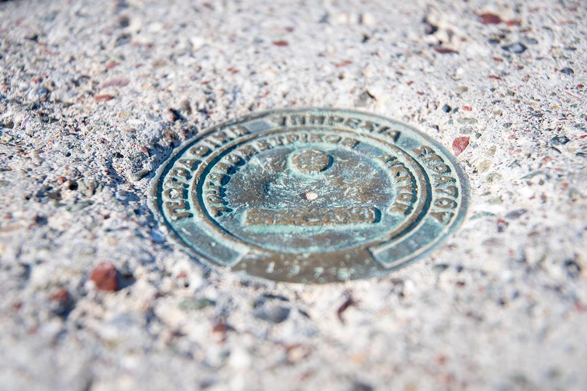 Окислившаяся медная метка круглой формы с нерасшифрованной надписью могла быть оставленной археологической экспедицией на Парсониси начала прошлого века.