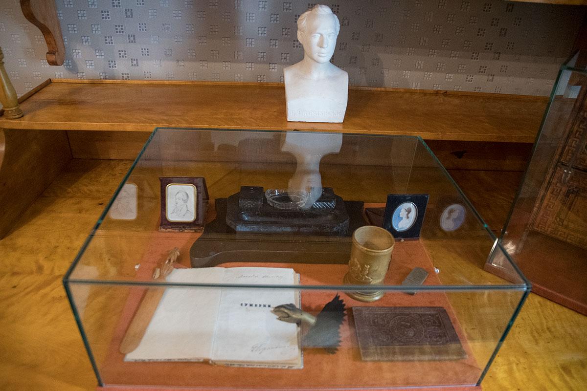 Крупным планом на фото показан рабочий стол Баратынского в усадьбе Мураново с его бюстом и накрытыми прозрачным кожухом личными вещами.