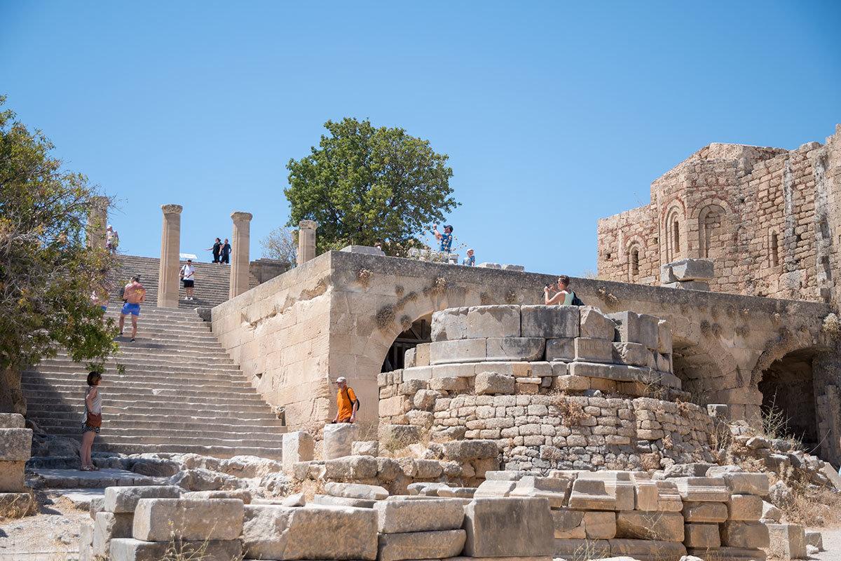 На выходе из средневековой арки перед Акрополем Линдоса сохранился постамент античности от памятника неведомому Аглаохарту, подарившему храму саженцы оливы.