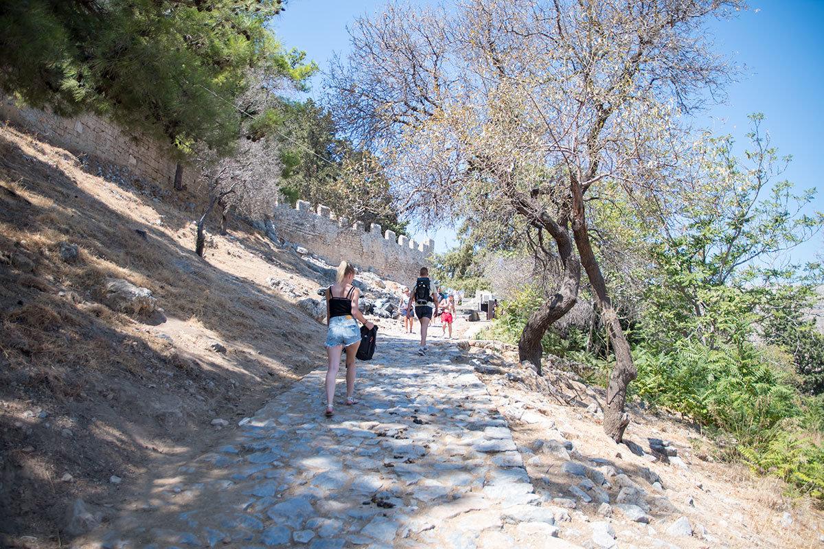 Дорога на Акрополь Линдоса вьется круговой спиралью вдоль крепостной стены, преодолеть путь можно пешком или верхом на ослике.