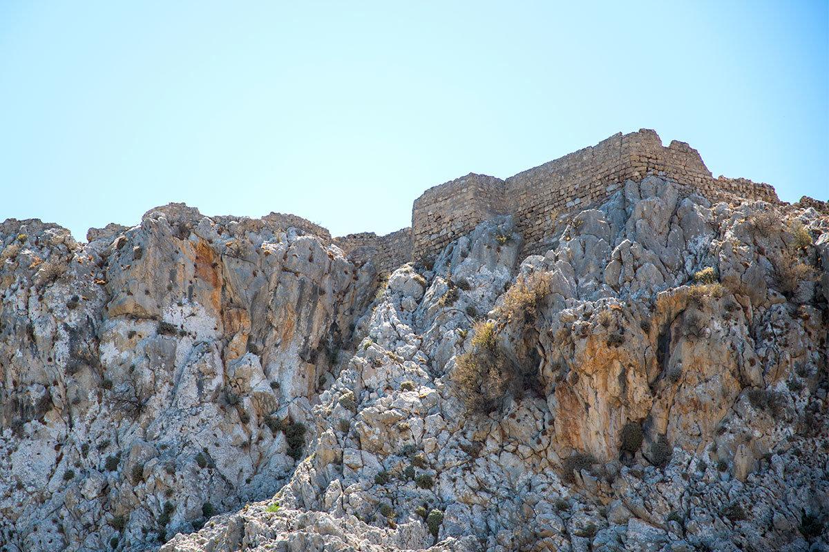 Увеличение масштаба изображения позволяет рассмотреть остатки каменных стен крепости Фераклос, словно вырастающие из горного массива.