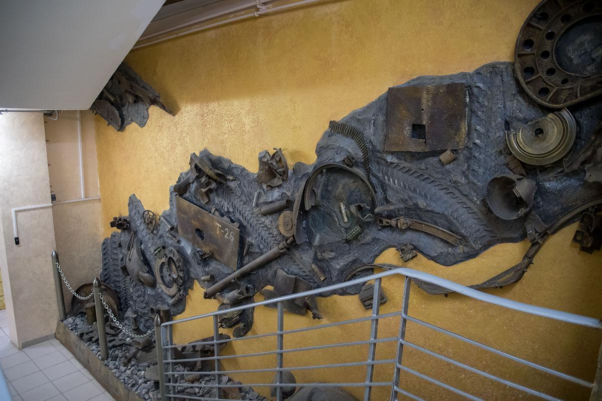 Военные дороги, на которых моторы войны оставили навсегда отпечатки протекторов и гильзы с обгорелыми деталями, изобразил коллаж у входа на экспозицию.