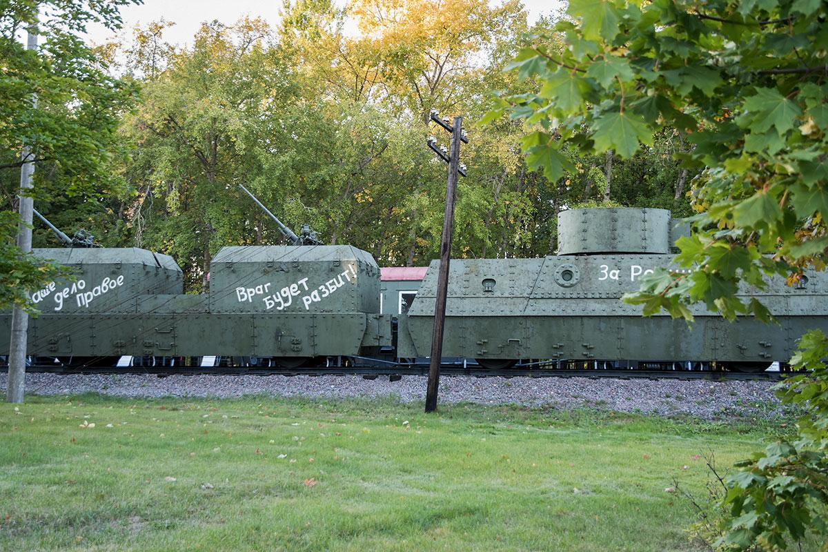 В разделе о железнодорожных войсках открытый музей военной техники демонстрирует платформы бронепоезда на рельсовых путях.