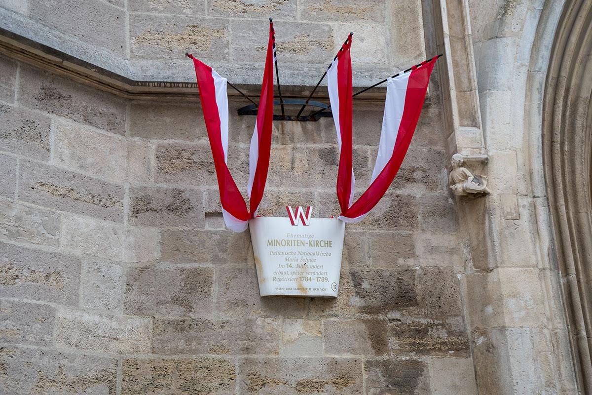 Историческая информация о церкви Миноритов содержит второе наименование храма, сведения о посвящении и времени последних изменений. Флаги – символы города Вены.