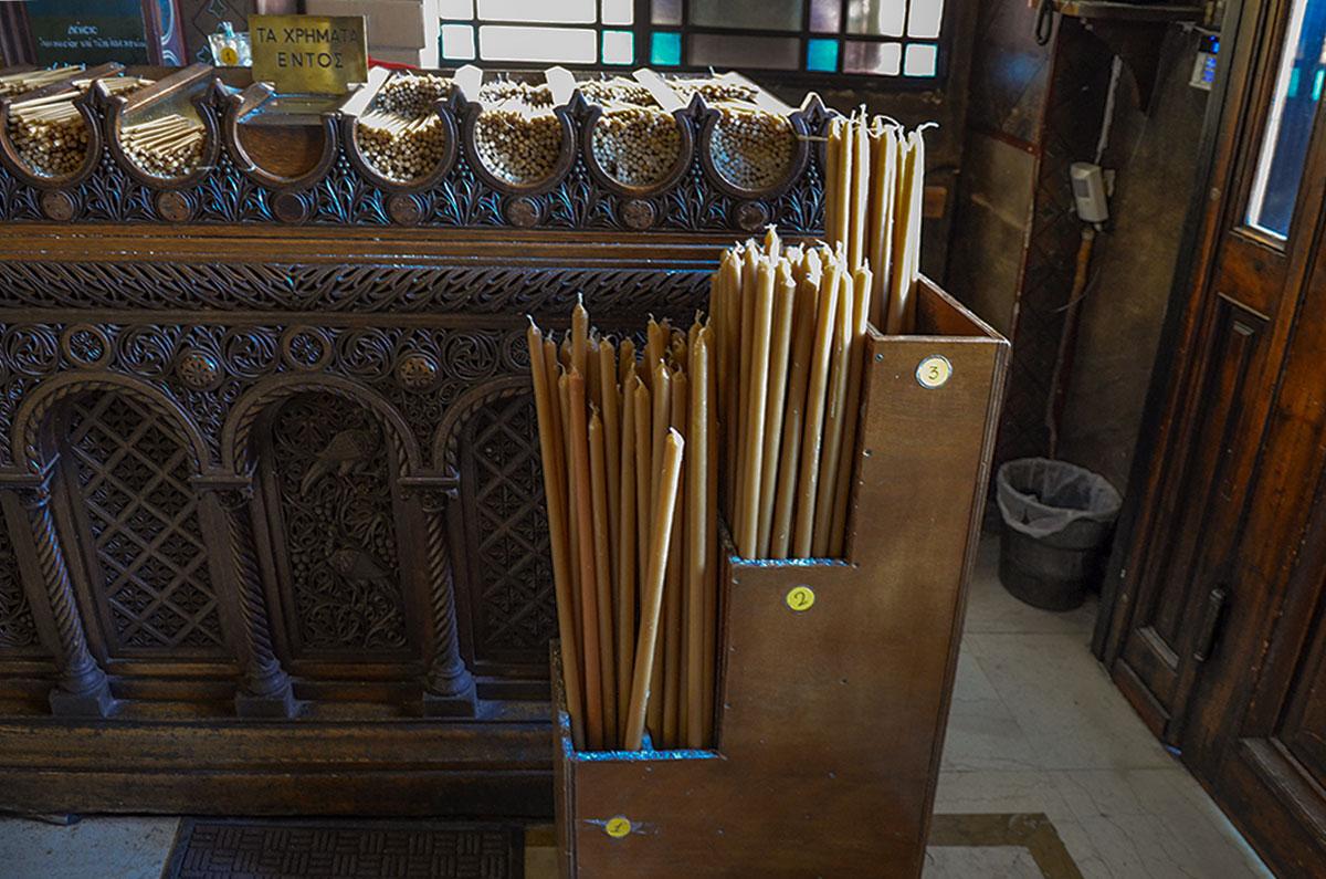 Свечной ящик греческой православной церкви виртуозно украшен, предлагает выбор свечей от стандартных до торжественных.