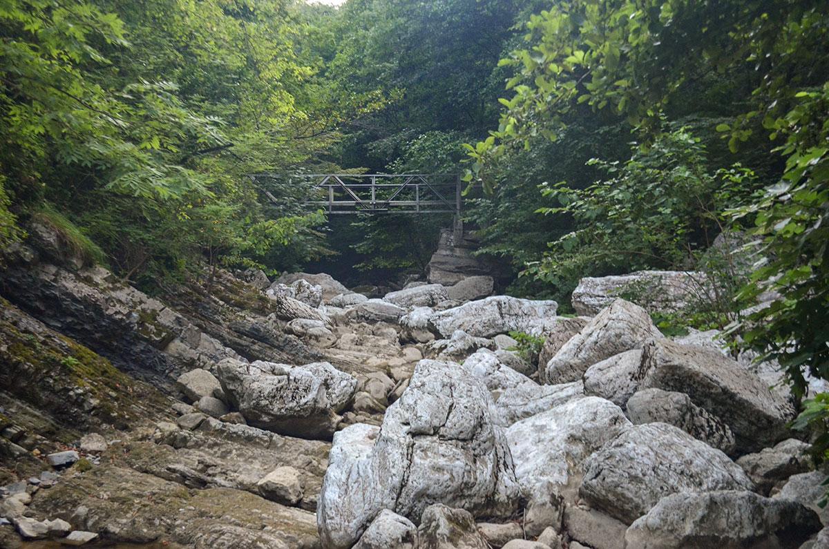 Речное русло вблизи мостика на пути к Агурским водопадам без воды напоминает огромный каменный желоб, наполненный валунами.