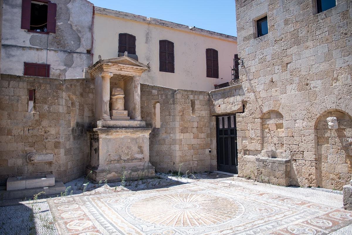 Южная часть второго двора Археологического музея Родоса демонстрирует прекрасный образец половой мозаики, пантеон в миниатюре на постаменте.