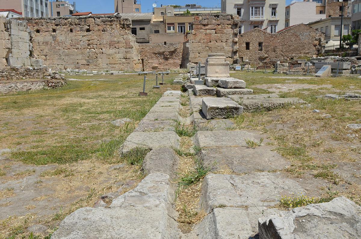 Через всю раскопанную территорию Библиотеки Адриана проложены плиты с углублением, предположительно для древних коммуникаций.