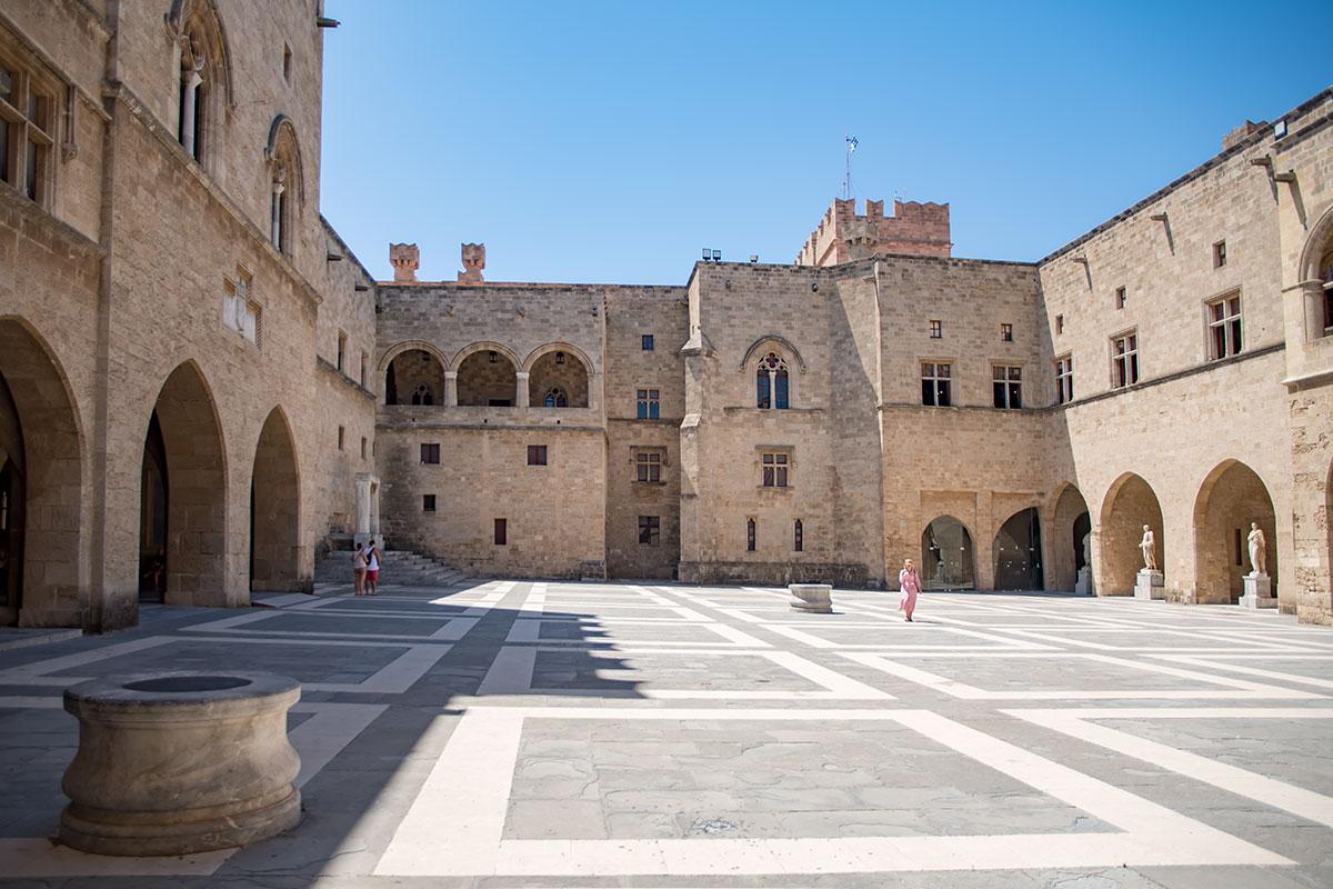 Живописен обширный внутренний двор Дворца великих магистров, здесь множество разнообразных архитектурных элементов.
