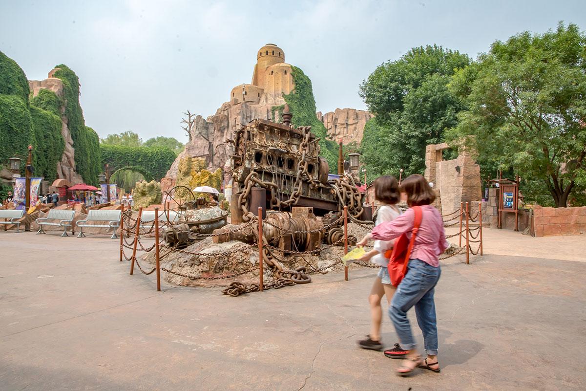 Возле пустующих скамеек уголка отдыха в парке Happy Valley в цепной загородке расположен своеобразный арт-объект, похожий на свалку металлолома.