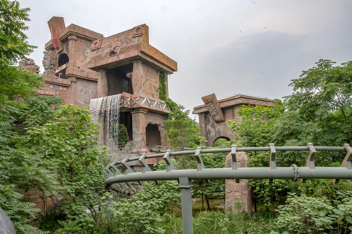 Фантазийный дворец майя в парке Happy Valley декорирован водопадом, через проем проходит трасса одного из многочисленных аттракционов.